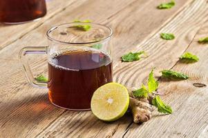 kopp te med ingefära, citron och mynta på träbord foto