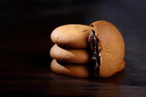 kex fyllda med chokladkräm. chokladkrämkakor. bruna chokladkex med krämfyllning på svart bakgrund. foto