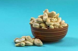 cashewnötter i en skål på blå bakgrund foto