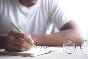 en student som skriver på anteckningsblock tidigt på morgonen foto