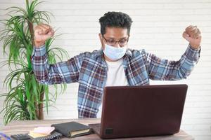 glad ung man i ansiktsmask som arbetar på bärbar dator foto