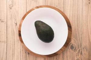 ovanifrån av skiva avokado på en tallrik på träbord foto