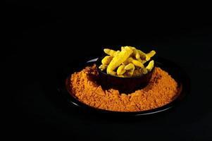 gurkmeja pulver och rötter eller bjälkar på svart bakgrund foto