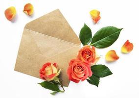 kuvert med rosor på en vit bakgrund. foto