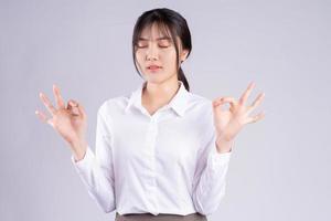 ung asiatisk kvinna tar djupa andetag för att hålla sig lugn foto