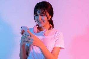 ung asiatisk tjej som spelar spel på telefon med spänning foto