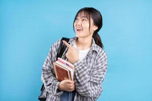 asiatisk kvinnlig student med lekfullt uttryck på blå bakgrund foto