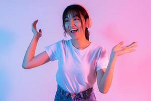 ung asiatisk tjej bär hörlurar och lyssnar på musik med spänning foto
