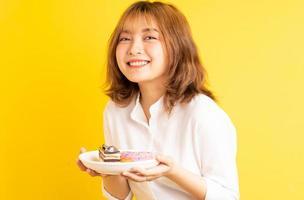ung asiatisk tjej som håller en tallrik med tårta med ett glatt uttryck foto