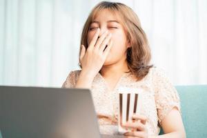 ung asiatisk tjej som sitter på soffan som äter och tittar på filmer på bärbar dator foto
