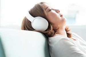 den unga flickan lutade sig tillbaka i soffan och njöt av musiken foto