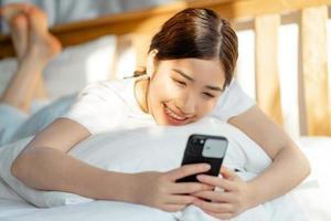 vacker asiatisk kvinna som använder sin telefon när hon bara vaknar foto