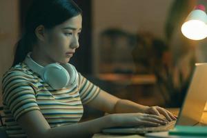 vacker asiatisk kvinna som försöker avsluta arbetet på natten foto