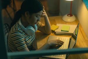 trött asiatisk kvinna som försöker få arbete gjort på natten foto