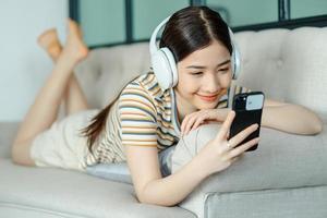 vacker asiatisk kvinna som ligger på soffan och lyssnar på musik medan du använder telefonen foto