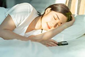 den vackra asiatiska kvinnan sov efter middagen med sin telefon bredvid sig foto