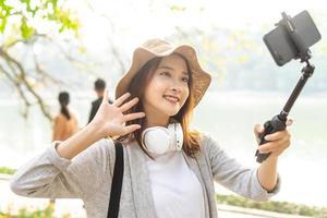 asiatisk kvinna som spelar in video på gatan i Hanoi, Vietnam foto