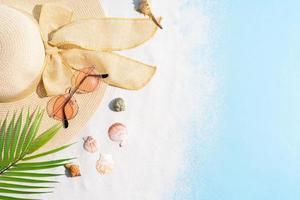 sommarbakgrund med hatt, solglasögon, sand och snäckskal foto