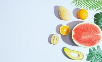 tropiska frukter som mango, apelsin, vattenmelon, avokado är ordnade på en vit bakgrund foto
