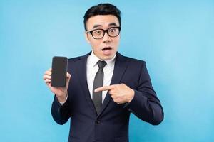 asiatisk affärsman bär kostym innehav smartphone på blå bakgrund foto