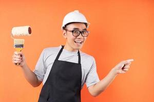 asiatisk målare som rymmer pensel som poserar på orange bakgrund foto