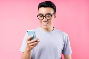 porträtt av asiatisk man med smartphone på rosa bakgrund foto