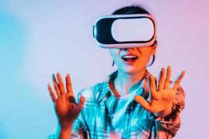 ung asiatisk kvinna bär VR-glasögon för att uppleva augmented reality-teknik foto