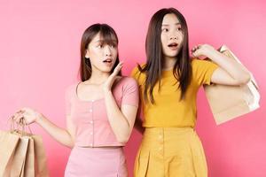 porträtt av två vackra unga asiatiska flickor som håller många påsar på rosa bakgrund foto