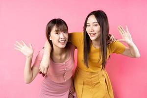 porträtt av två vackra unga asiatiska flickor som poserar på rosa bakgrund foto