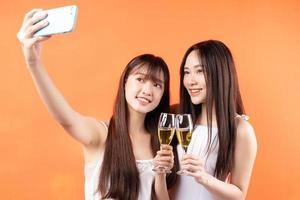 två vackra unga asiatiska flickor som lyfter vinglas på orange bakgrund foto