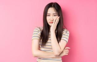 ung asiatisk kvinna som poserar på rosa bakgrund foto