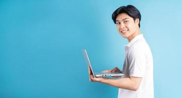asiatisk man skriver på en blå bakgrund foto