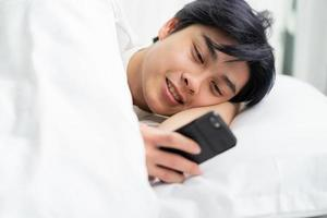 asiatisk man som ligger i sängen och använder telefonen foto