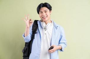 manlig asiatisk student som ler och skapar ok symbol i handen foto