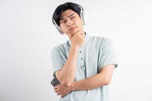 den asiatiska mannen lyssnade på musiken och verkade tankeväckande foto