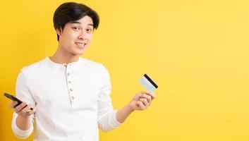 asiatisk man med ett bankkort i handen på en gul bakgrund foto
