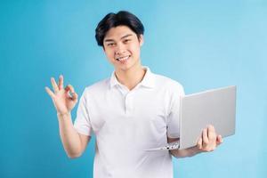asiatisk man som håller sin bärbara dator och visar ok-symbolen i handen foto