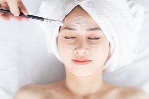 asiatisk kvinna som gör skönhetsbehandlingar, spabehandlingar och appliceras kräm i ansiktet foto
