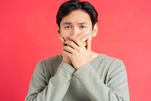 ett foto av en stilig asiatisk man som täcker munnen för att inte missa någon annans hemlighet