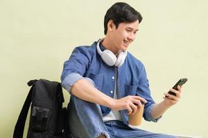 stilig asiatisk studentpojkesammanträde med smart telefon foto