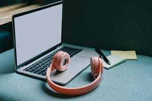 bild av bärbar dator med vit skärm och rosa hörlurar bredvid foto