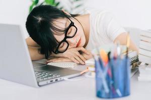 asiatisk affärskvinna är trött och har huvudvärk med mycket arbete på deadline foto