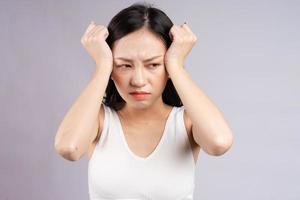 asiatisk kvinna som lider av huvudvärk foto