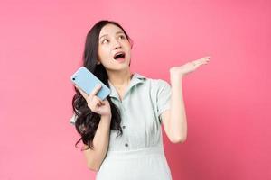 ung asiatisk kvinna som håller telefonen och ser upp med spänning foto