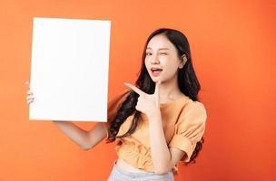 ung asiatisk kvinna med vit tavla på orange bakgrund foto