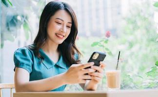 ung asiatisk kvinna som använder smartphonen för att arbeta på café foto