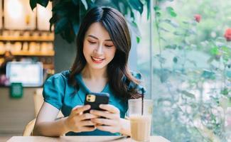 ung asiatisk kvinna som ler medan du använder smartphonen foto