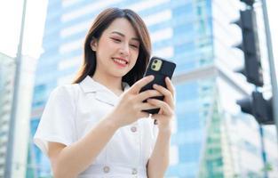 ung asiatisk kvinna som går och använder smartphone på gatan foto