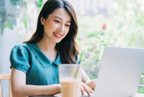 ung asiatisk kvinna som använder bärbara datorn på kaféet foto