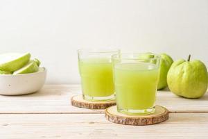 färskt guavajuiceglas med färsk guavafrukt på träbord foto
